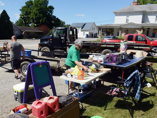 Rich Meese, left, and wife Kim place price tags on items on Wednesday at the Christian Life Center during the National Road Yard Sale. The event, which was originally postponed due to COVID-19, will run through Sunday.