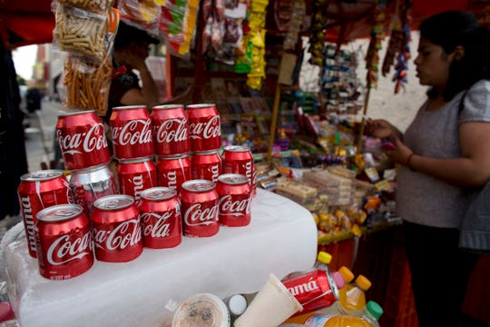 Cans of Coca-Cola sit on an ice block to keep cool at a street vendor's stand in Mexico City in 2014.