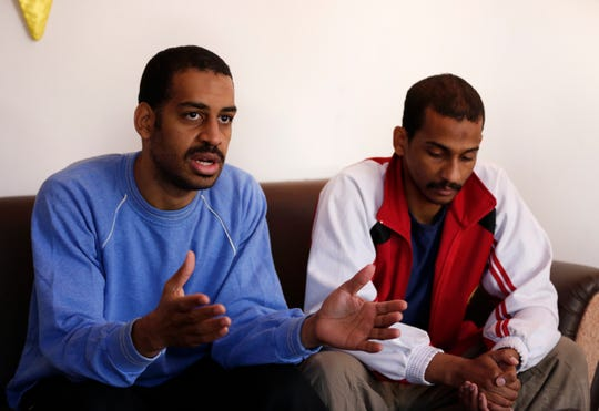 """Alexanda Amon Kotey, left, and El Shafee Elsheikh, who were allegedly among four British jihadis who made up an Islamic State cell dubbed """"The Beatles,"""" speak during an interview with The Associated Press at a security center in Kobani, Syria."""