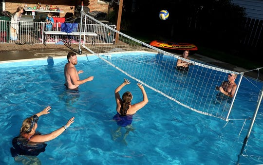 Gina Burnside plays volleyball with her neighbors in her swimming pool, which she rents out using the Swimply app. From left: Dawn Weimer; Chris Freeman; his wife Brittany Freeman; Gina Burnside; and Dawn's husband Robert Weimer.