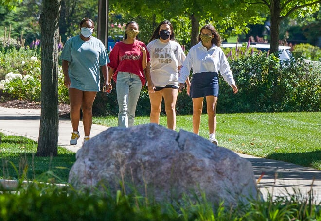 Students wearing masks walk on campus of the University of Notre Dame on Aug. 18, 2020, in South Bend, Ind.  The University of Notre Dame on Aug. 18 canceled in-person undergraduate classes for two weeks after a spike of coronavirus cases that occurred since the semester began.