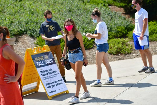 Incoming freshmen wait in line to ask questions at an informational tent while arriving on campus at University of Colorado Boulder on Aug. 18, 2020 in Boulder, Colo..