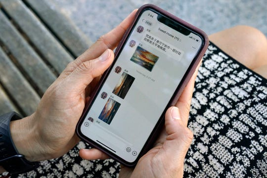Sha Zhu, of Washington, shows the app WeChat on her phone, which she uses to keep in touch with family and friends in the U.S. and China on Aug. 18, 2020, in Washington.