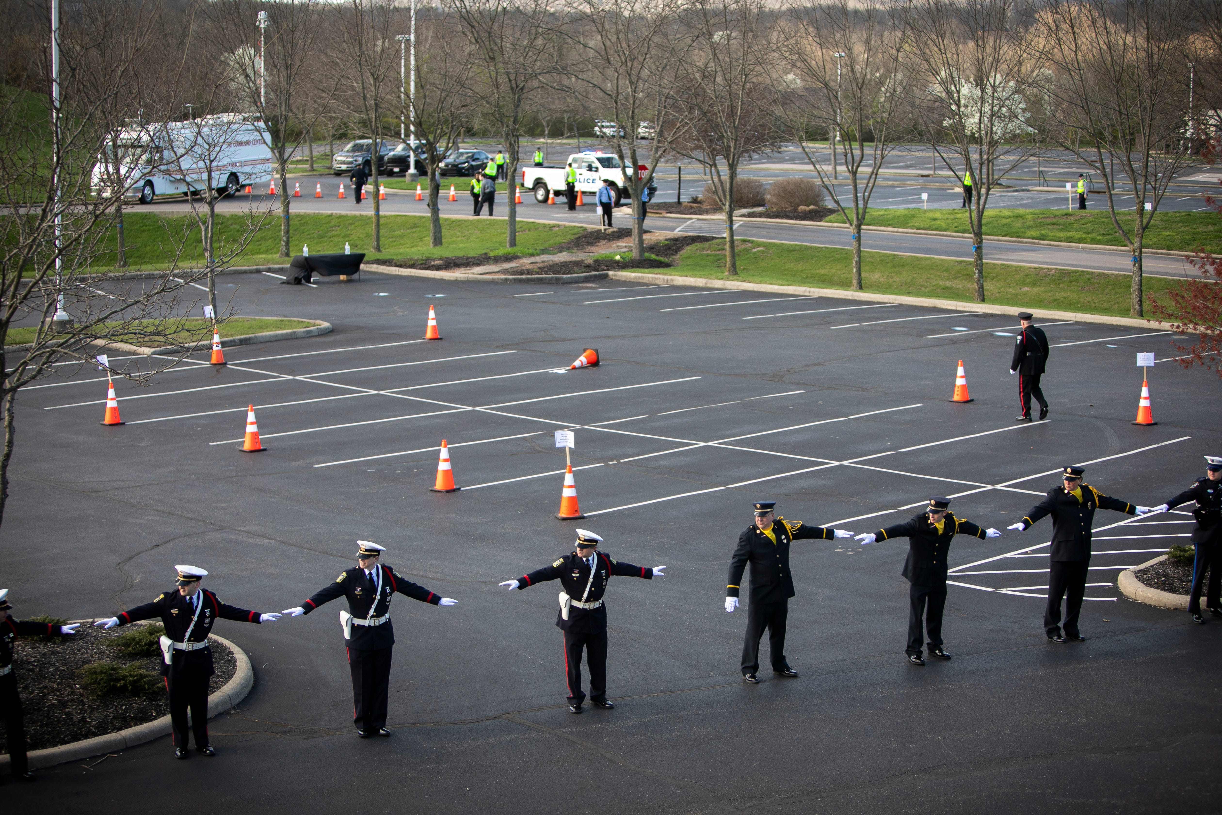 Police follow social distancing guidelines outside Vineyard Church in Springdale, Ohio, to honor Officer Kaia Grant.