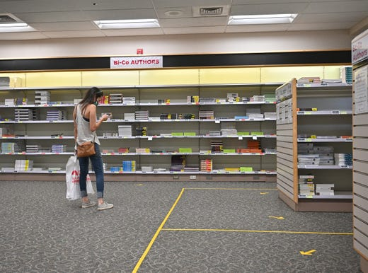 A student checks her phone while shopping for textbooks as classes begin amid the coronavirus (COVID-19) pandemic on the first day of the fall 2020 semester at the University of New Mexico on Aug. 17, 2020 in Albuquerque, N.M..