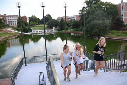 Faith Spino, Darcy Roberts and Abby Helliburton walk by the Cooper Library and reflection pond during a morning walk early, before their first day of fall classes at Clemson University in Clemson, S.C., Aug. 19, 2020.