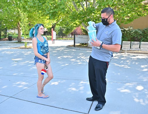 Jose Villar (R) gives a mask to Savannah Sickler, a freshman, as students begin classes amid the coronavirus (COVID-19) pandemic on the first day of the fall 2020 semester at the University of New Mexico on Aug. 17, 2020 in Albuquerque, N.M..