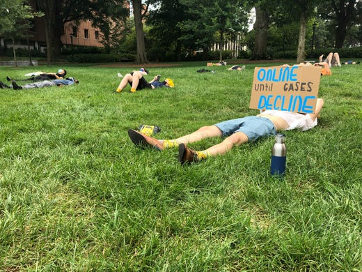 """A protester holds a sign opposing in-person classes Aug. 17, 2020, at a """"die-in"""" at Georgia Tech in Atlanta."""