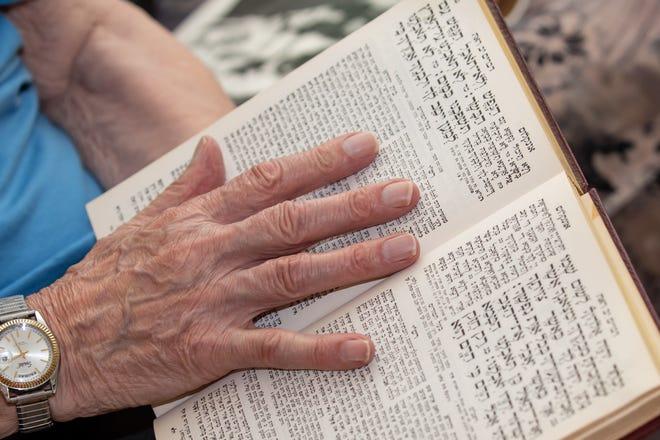 Ernie Gross, a holocaust survivor living in Philadelphia, leafs through the pages of a Siddur prayer book.