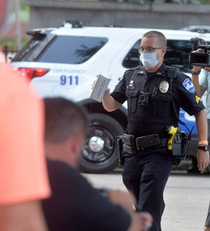 Cpl. William Barnett hands out face masks to those needing one in City Market on Wednesday.
