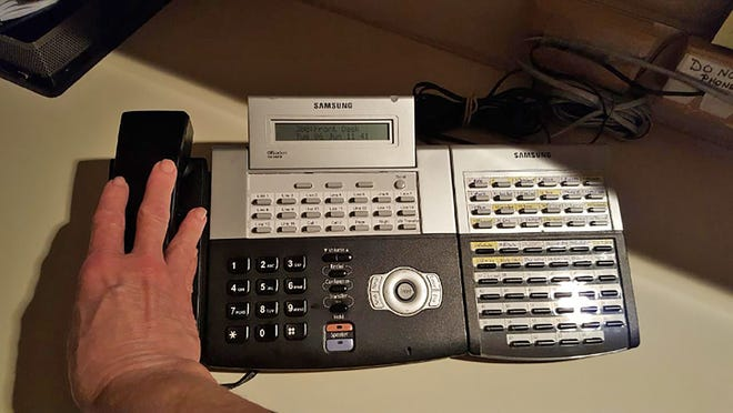 A fully operating telephone sits on a desk in an office ready for use.