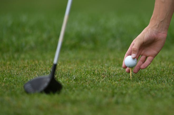 A golfer tees his golf ball on the tee.