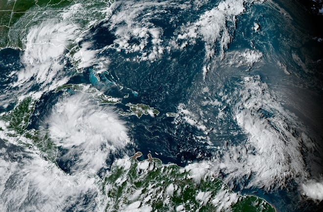 A satellite image shows tropical storms 14 (lower left) and 13 (lower right) Thursday afternoon.