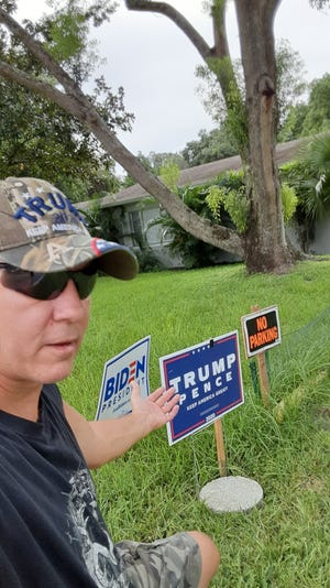 Anthony Vullo shows one of the new Trump signs someone dropped off at his home.
