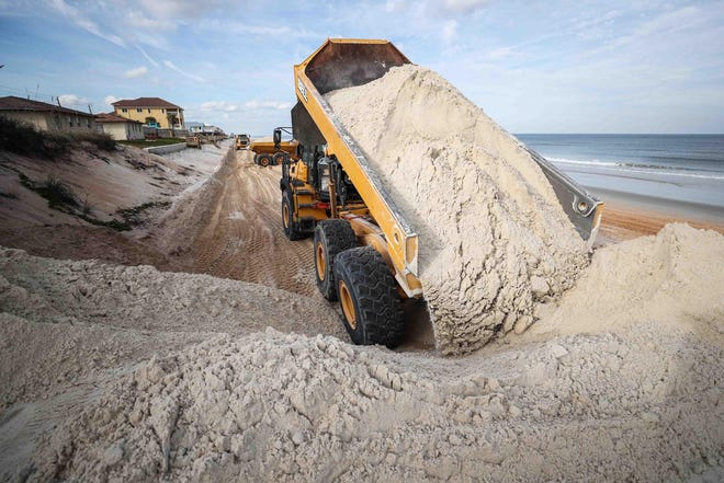 Trucks dump sand on the beach in an earlier phase of the dune-restoration efforts in Flagler County. News-Journal file