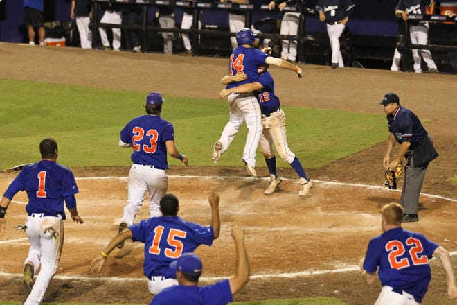 Bolles' Taylor Betros (14) scores the winning run against Gulliver Prep as Caleb Denmark (12) and Bulldogs teammates celebrate at the 2010 FHSAA Class 3A baseball championship in Port St. Lucie.