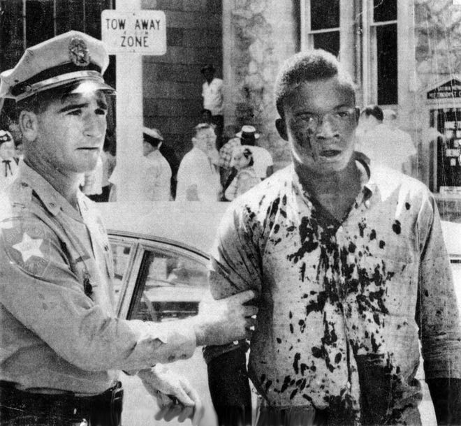 A Jacksonville police officer helps Charlie Griffin, a teenager who was shopping downtown, after he was struck in the head with an ax handle during the civil unrest Aug 27, 1960, on what has come to be known as Ax Handle Saturday.
