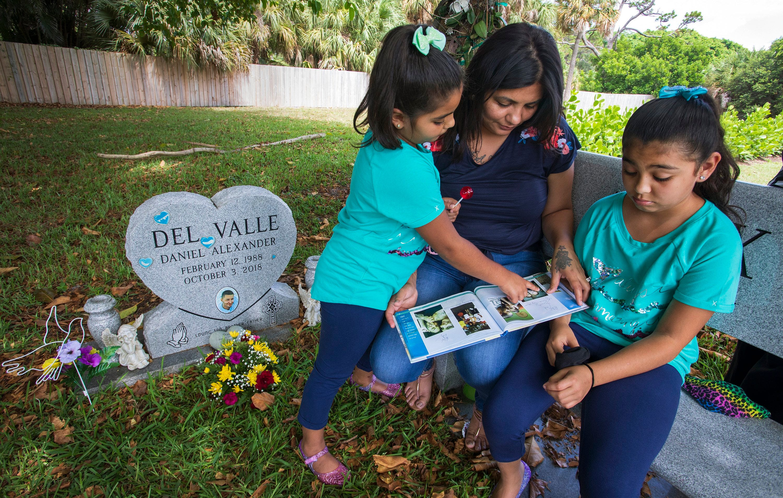 Lily Burke, with her and Daniel Del Valle's daughters, Lily and Daniela, look at a photo book at Daniel's gravesite in West Palm Beach on July 2, 2020. He was killed in October 2018.