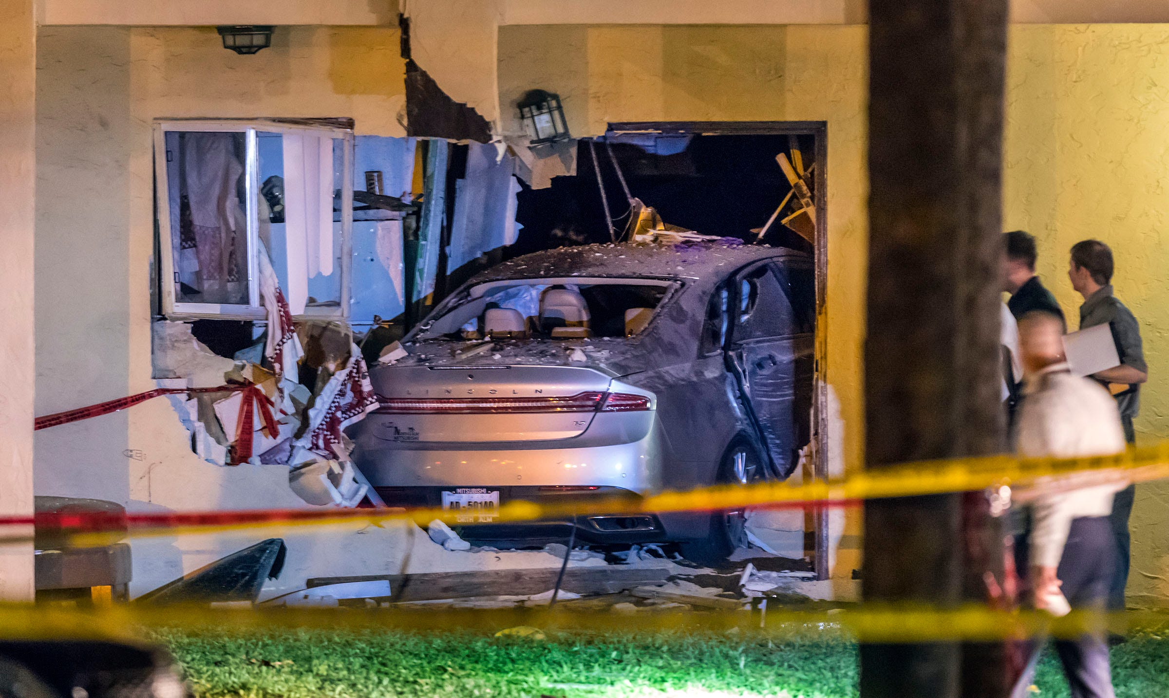 Deputies examine the scene where two men died after their car slammed into a home in a Greenacres-area apartment complex early on Oct. 3, 2018, following a shooting.