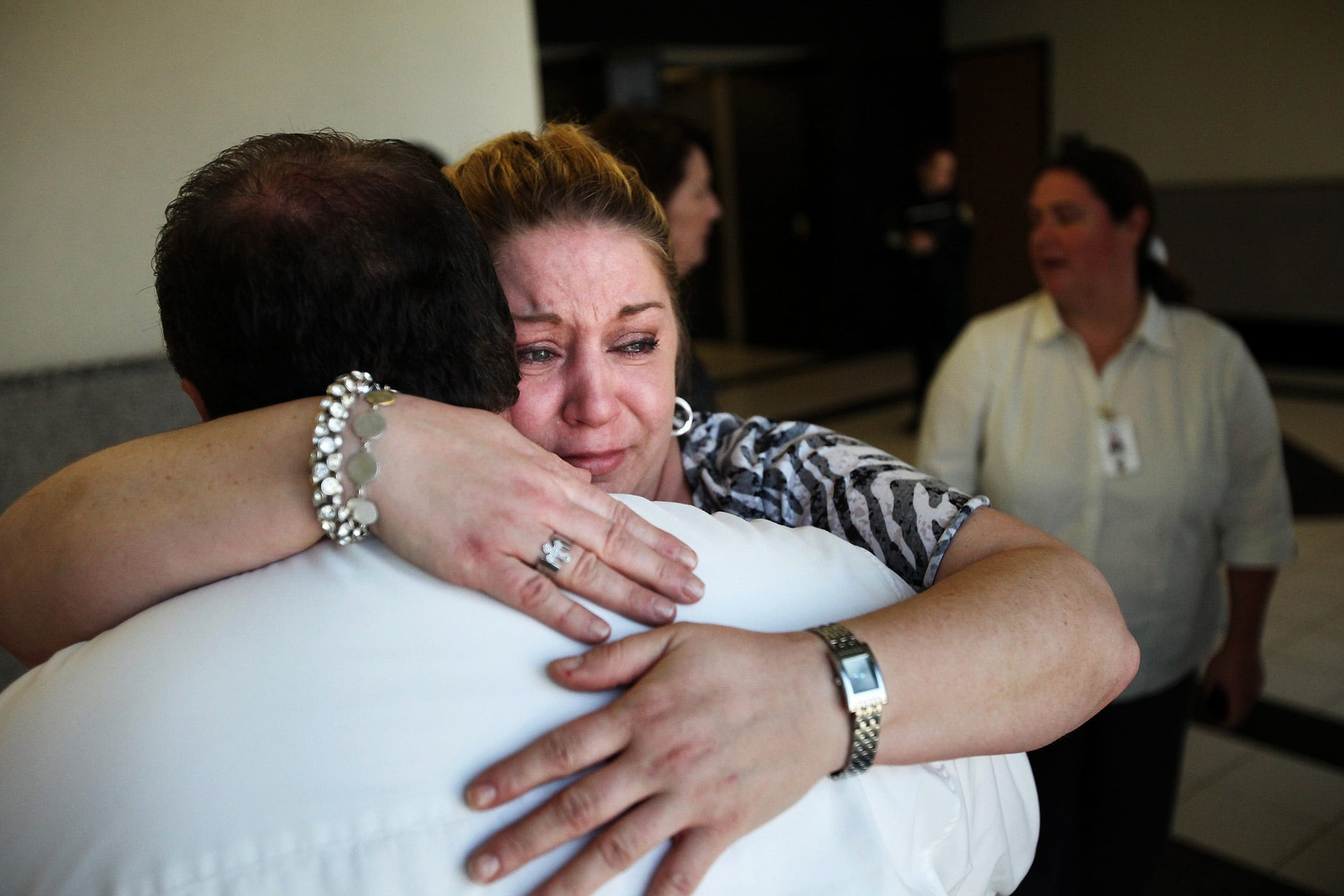 Robert Harrison's sister, Dawn Harrison, hugs a detective after Daniel Alexander was found guilty Jan. 11, 2011, of killing Robert Harrison during a fight at their Palm Beach Gardens home.