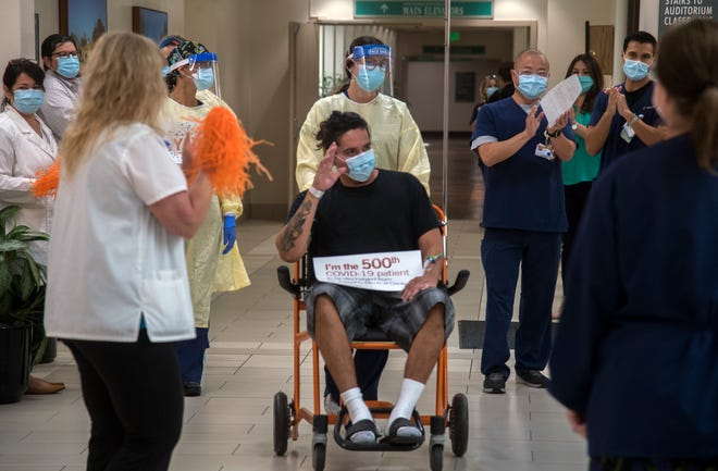 Louis Aguirre is pushed in a wheelchair by registered nurse Samantha Belso as he cheered on by the staff at St. Joseph's Medical Center in Stockton. Aguirre was the 500th patient to recover from COVID-19 and discharged from the hospital.