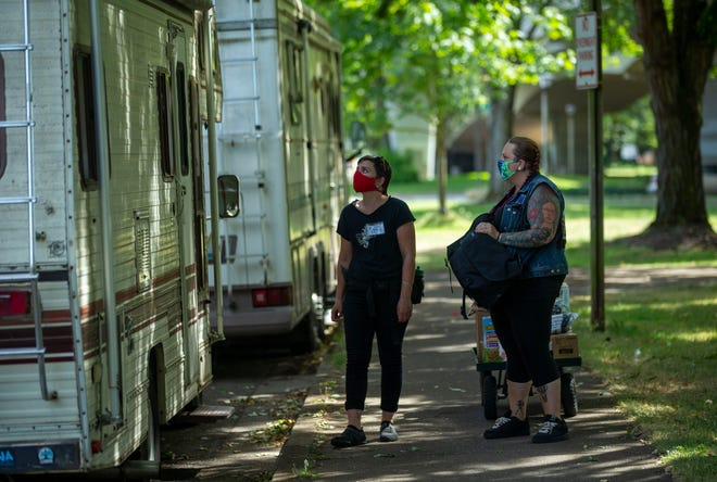 Rebecca Krop, left, and Brittiny Raine, co-founder of Community Outreach Through Radical Empowerment, known as CORE, pause at an RV on Aug. 19 parked along Jefferson Street to see if the person in the vehicle needs any supplies.