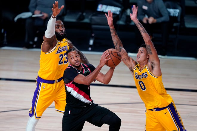 Portland's CJ McCollum looks for an opening between Los Angeles Lakers forwards LeBron James (23) and Kyle Kuzma (0) during the first half of Tuesday's game in Lake Buena Vista, Fla. Game 2 of the first-round playoff series is Thursday. [AP Photo/Ashley Landis]
