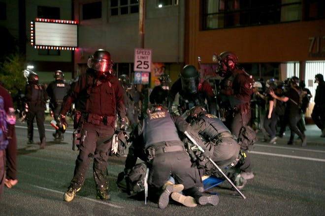 Portland police declare a riot at the Multnomah County Building, on Tuesday, Aug. 18, 2020, in Portland. Officers made at least two arrests of protesters. (Beth Nakamura/The Oregonian via AP)