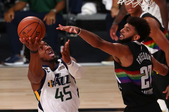 Utah's Donovan Mitchell (45), who had 30 points, drives to the basket against Denver's Jamal Murray during Utah's 124-105 playoff win Wednesday in Lake Buena Vista, Fla. [AP Photo/Kim Klement]