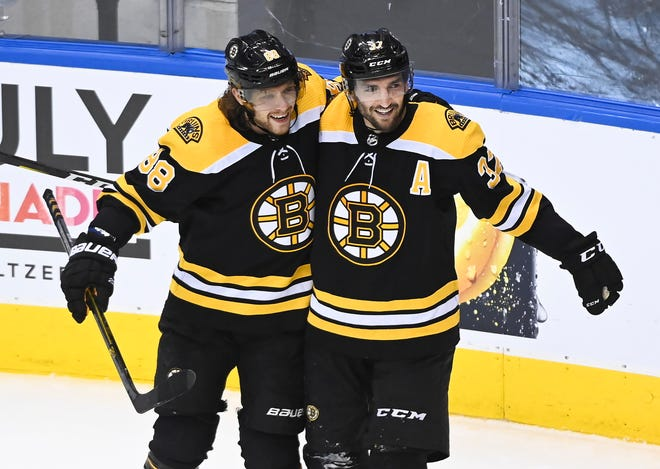 Boston's Patrice Bergeron, right, celebrates his goal with teammate David Pastrnak during second period of Wednesday's playoff win over the Carolina Hurricanes in Toronto. [Nathan Denette/The Canadian Press via AP]