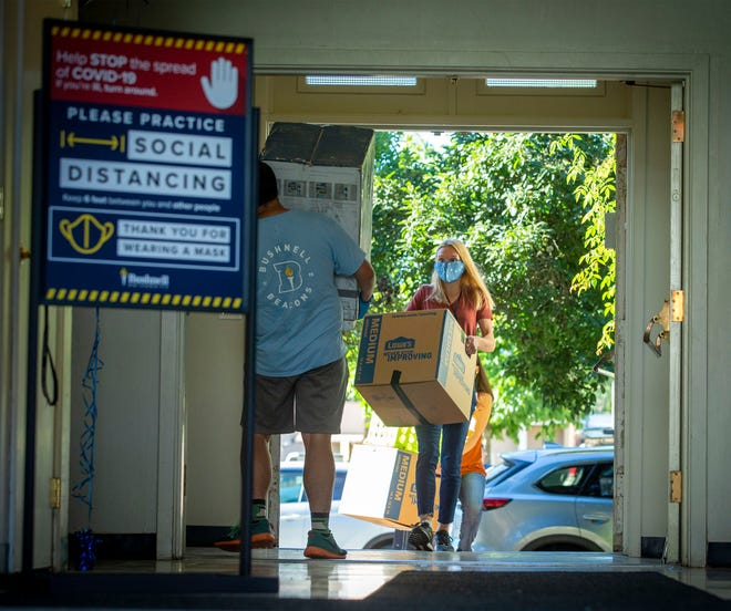 Hannah Love, an incoming freshman at Bushnell University, follows Kilano Loyd as he carries her refrigerator up to her dorm room on the Eugene campus on Thursday.