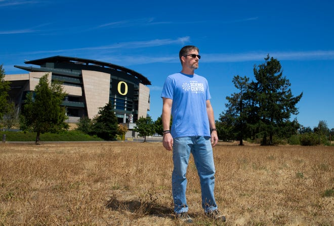 Tim Scott, director of The Science Factory in Eugene, stands in a field that is usually available for parking during Oregon football games.