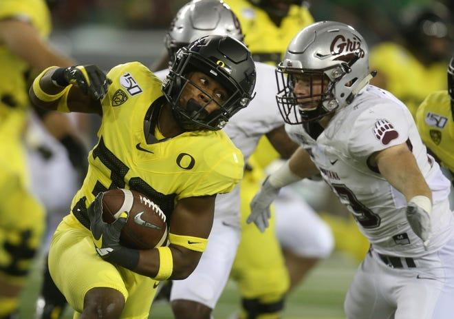 Oregon's Jaylon Redd, left, runs around Montana's Josh Sandry during the first quarter of a Sept. 14 game at Autzen Stadium. [Chris Pietsch/The Register-Guard]
