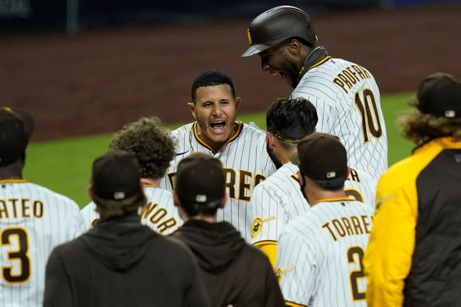 San Diego's Manny Machado, center, reacts after hitting a walk-off grand slam during the 10th inning of Wednesday's game against the Texas Rangers in San Diego. The Padres won 6-3. [AP Photo/Gregory Bull]
