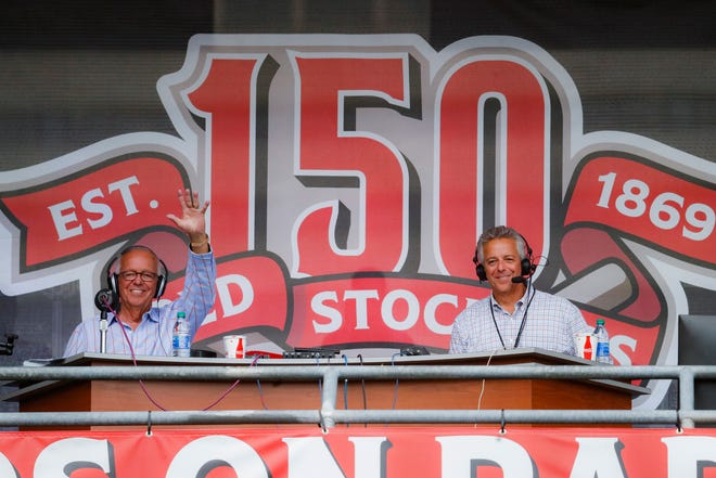 Cincinnati Reds radio announcer Marty Brennaman, left, waves next to his son Thom, in a special outside booth before the Reds' baseball game against the Milwaukee Brewers on Sept. 25, 2019, in Cincinnati. [AP Photo/John Minchillo, File]