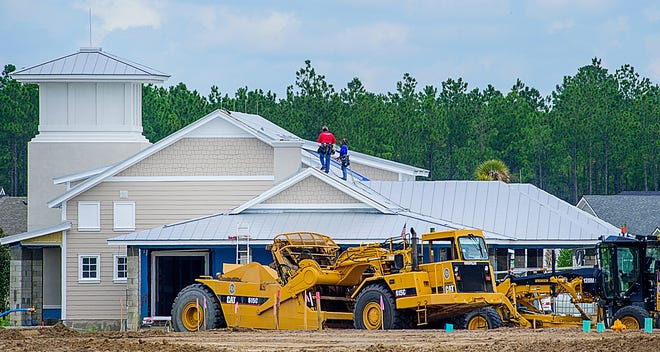 Construction workers work on a roof of a building under construction in the Silverleaf development, north of St. Augustine, on Thursday. [PETER WILLOTT/THE RECORD]