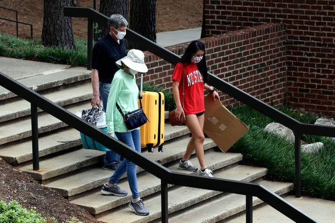 Charles and Carrie Jacocks and incoming freshman Ann Grace, right, carry their belongings as college students begin moving in for the fall semester at N.C. State University in Raleigh on July 31. [AP Photo/Gerry Broome]
