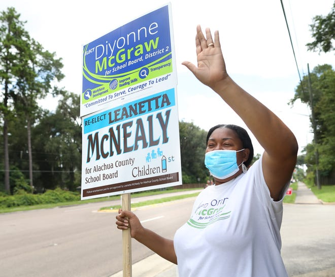 Dionne McGraw, who won election Tuesday to the Alachua County School Board, waves to motorists as she campaigns outside the Grace United Methodist Church in Gainesville.