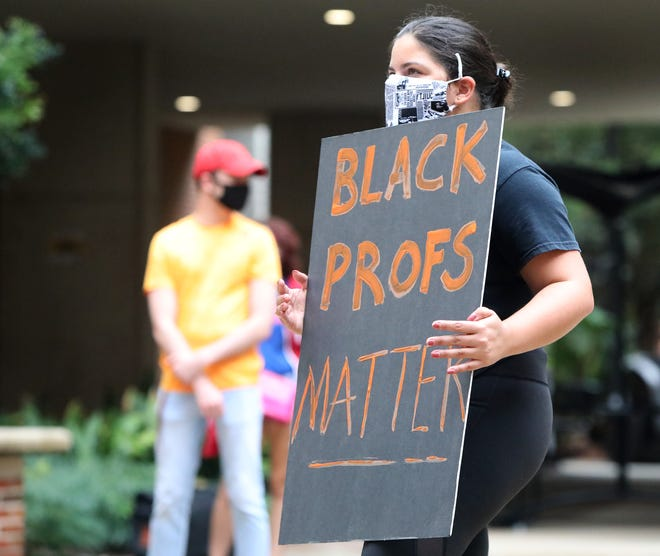 A student holds a sign Thursday as a group protests Professor Michelle Jacobs not being allowed to teach remotely at the University of Florida Levin College of Law. Jacobs, who is Black, teaches several law classes that deal with race. [Brad McClenny/Staff photographer]