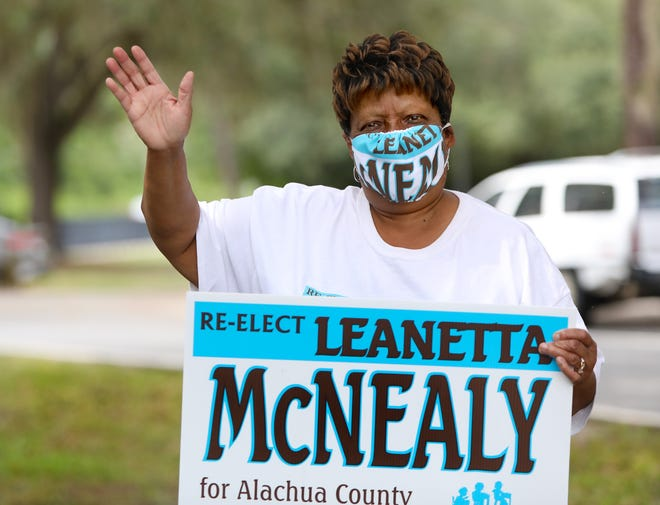 Leanetta McNeal, who was reelected Tuesday to the Alachua County School Board, waves as she campaigns on Election Day outside the T.B. McPherson Center in Gainesville.