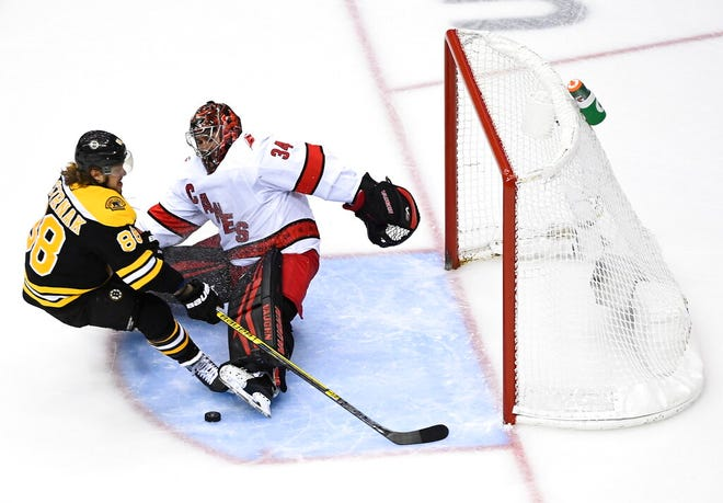 Carolina Hurricanes goaltender Petr Mrazek (34) makes break-a-way save against Boston Bruins right wing David Pastrnak (88) during second period NHL Eastern Conference Stanley Cup playoff hockey action in Toronto on Wednesday, Aug. 19, 2020. (Nathan Denette/The Canadian Press via AP)