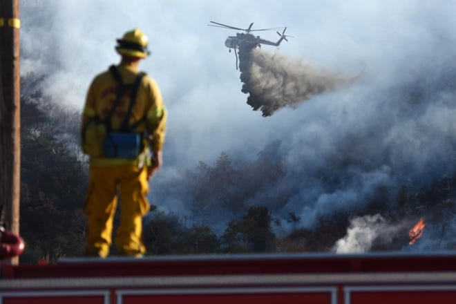 A firefighter watches a helicopter douse water while battling the Bluecut Fire that burned more than 36,000 acres in the Cajon Pass in August 2016.