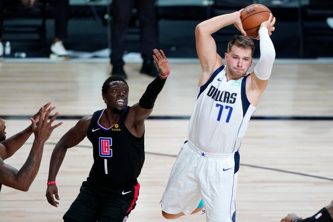 Dallas Mavericks' Luka Doncic looks to pass the ball as he is guarded by Los Angeles Clippers' Reggie Jackson during the first half Wednesday, Aug. 19, 2020, in Lake Buena Vista, Fla.