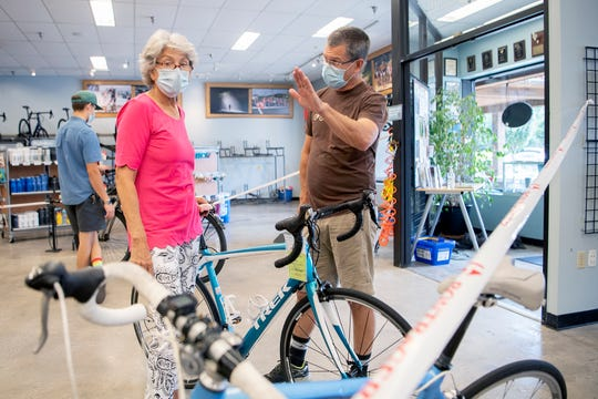 Billie Messer, of Lake Toxaway, looks at her current bike as Sam Messer explains the difference in fit to the one she came into Liberty Bicycles to possibly purchase on Aug. 19, 2020. Bicycles have been in short supply due to the coronavirus pandemic.