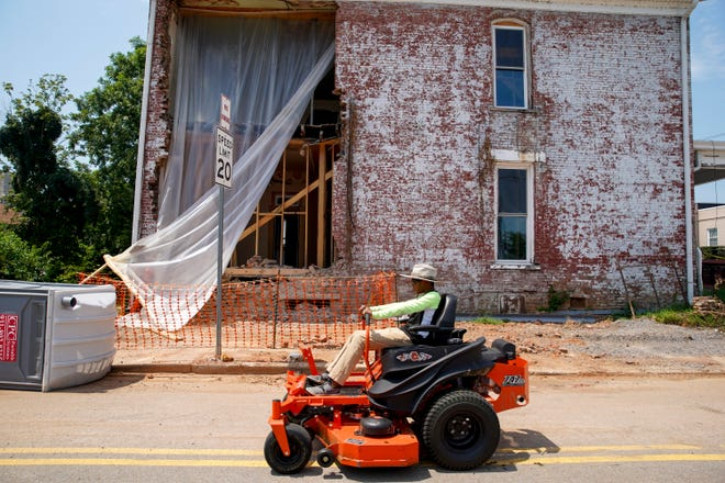 A landscape worker drives by on their mower in front of the partially taken down brick wall undergoing renovation at the old Methodist Church in Clarksville, Tenn., on Monday, Aug. 10, 2020.