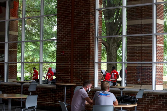 Students sit in a sparsely populated hall while the drum line practices outside at Austin Peay State University in Clarksville, Tenn., on Wednesday, Aug. 19, 2020.