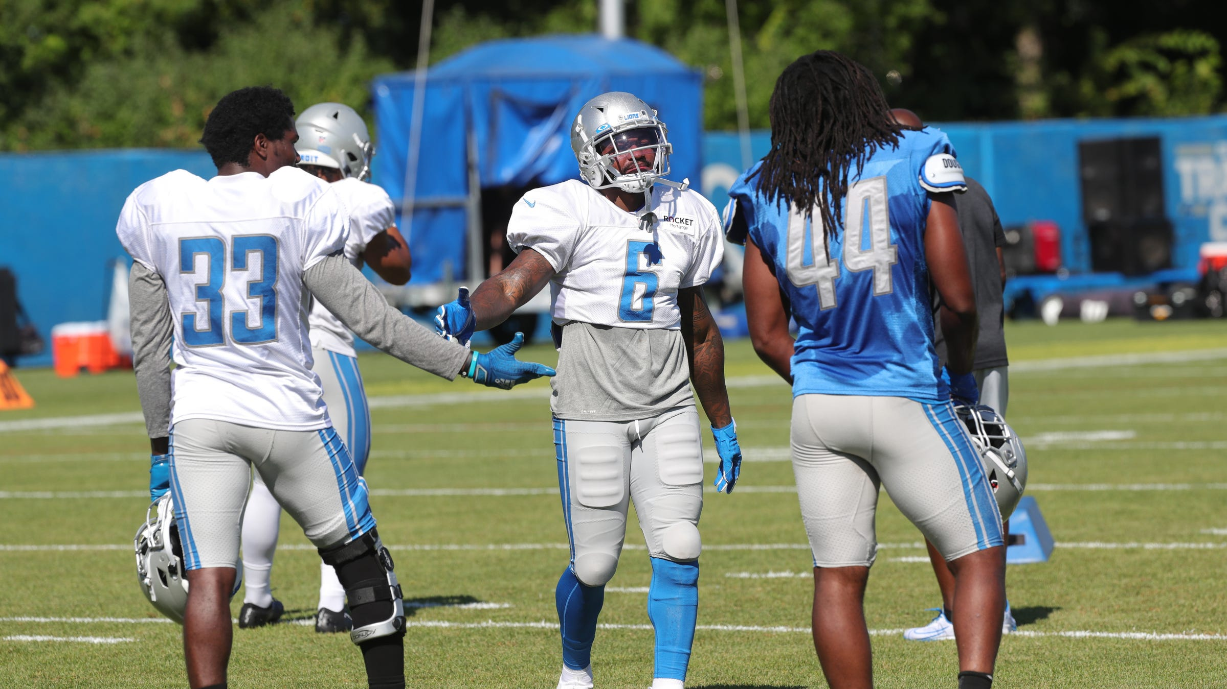 Running backs Kerryon Johnson (33) and D'Andre Swift (6) talk with linebacker Jalen Reeves-Maybin during Detroit Lions training camp Thursday, August 20, 2020 in Allen Park.