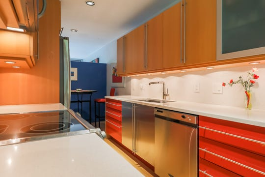The long, galley kitchen keeps its original design, but with new surfaces of beech wood, red-orange lacquered drawers and white quartz counters. The blue wall at the rear shows the low profile, which lets in sunlight.