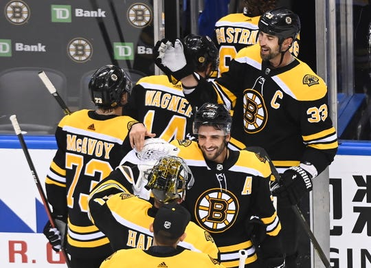Boston Bruins defenseman Zdeno Chara (33) and Bruins center Patrice Bergeron (37) celebrate with teammates after eliminating the Carolina Hurricanes during third period NHL Eastern Conference Stanley Cup playoff hockey action in Toronto on Wednesday, Aug. 19, 2020.
