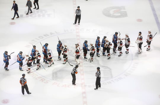 Players from the Colorado Avalanche and the Arizona Coyotes shake hands after Game 5 of an NHL hockey first-round playoff series in Edmonton, Alberta, Wednesday, Aug. 19, 2020.